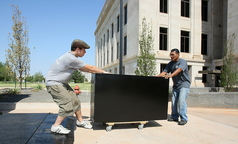Ben Poynter and Arlando Montes with ACE Transfer & Storage move furniture into the new Supreme Court building Friday. PHOTO BY MAIKE SABOLICH