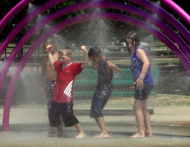Keeping cool in the 100+ degree heat Aiden Carter, Ramond Wilcox and Abigail Carter  stand under a water rainbow at the  RiverParks Water Park in South Tulsa.