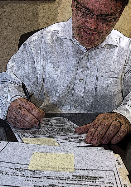 Stephen Karbelk, CEO of National Commercial Auctioneers, works on paperwork in his Tulsa Office.