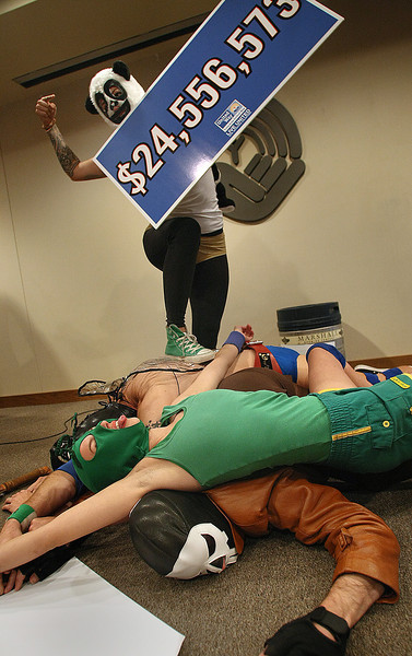 La Randita Bonita stands on a pile of Luchadors who dared to bring in too low of a goal for the 2011 United Way fundraising goal.   The goal of $24,556,573 was approved by the board of directors.