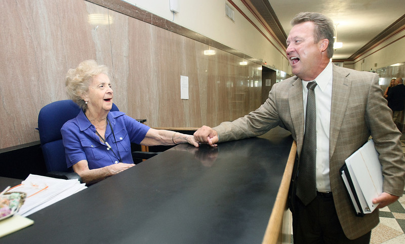 Attorney Randy Lee Bumgarner, right, says hello to Mary Lou Starke at the court house information desk Wednesday.  Bumgarner calls Starke the heart of the court house. PHOTO BY MAIKE SABOLICH
