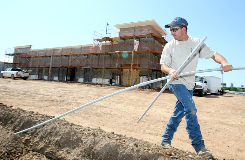 Mark Kiker with Advanced Electric works on the construction site of the new Crossroads Roofing facility on Santa Fe, next to the old location. PHOTO BY MAIKE SABOLICH