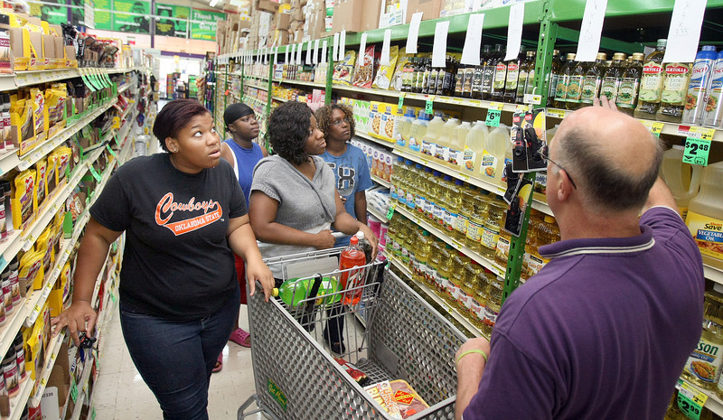 Buy For Less Store Manager George Harrison, right, gives a tour of healthy food choices to shoppers Neicy Hudson, Mae Hughes, Rai-Rae Hudson and Brittany Emery Tuesday at the store on NE 23rd Street. PHOTO  BY MAIKE SABOLICH