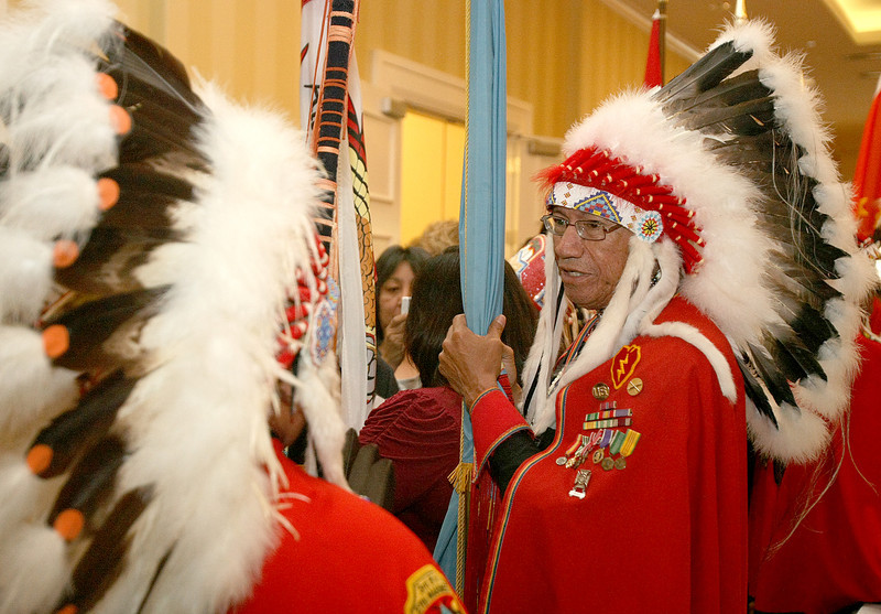 Darwin Palmer with the Kiowa Black Leggins Color Guard before the opening ceremony of the sovereignty Summit at the Skirvin Wednesday. PHOTO BY MAIKE SABOLICH