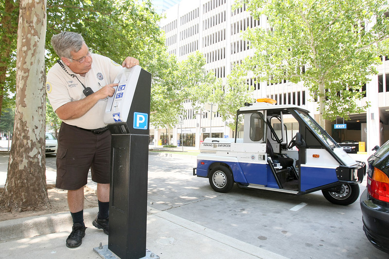 Ronnie Brackett, police service technician, explains a parking meter on Main Street Tuesday. .PHOTO BY MAIKE SABOLICH