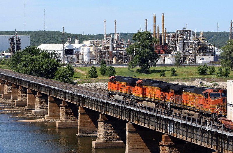 A BNSF train crosses the Arkansas River to the rail yard and oil refineries on the West bank of the river in Tulsa.