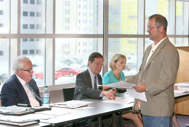 Developer Gary Brooks, right, hands out papers to the Oklahoma City Urban Renewal Authority detailing his proposal for the old Mercy Hospital site in Midtown Thursday at the downtown library.  PHOTO BY MAIKE SABOLICH
