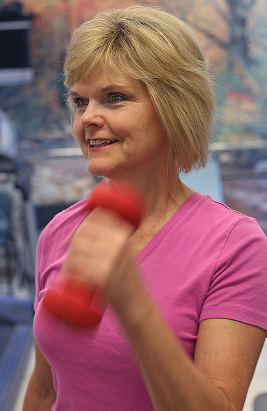 Debbie Ratliff lifts weights at the onsite gym at the Lafarge Cement complex in Tulsa.