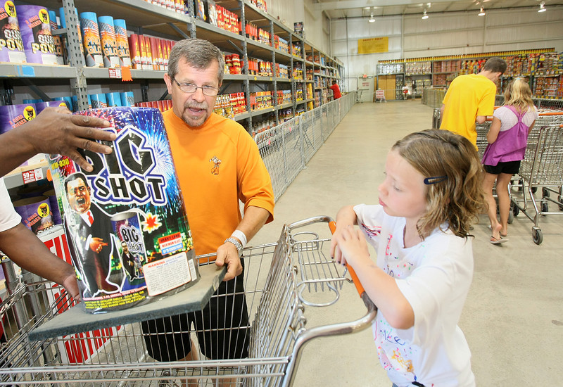 Jimmy Durant, spokesperson for Fireworks Warehouse, is fireworks shopping with his children Wednesday.  Pictured to the right: Kelsie Damrill. PHOTO  BY MAIKE SABOLICH
