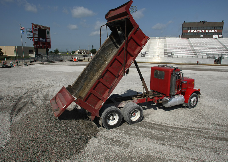 A dump truck delivers part of the 3000 tons of gravel used as a foundation for a turf replacement project at the Owasso High school football stadium.