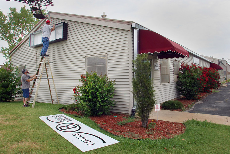 Bob Bergeron and Hank Maydell install new signage for Circle B Measurements on their new location in West Tulsa.