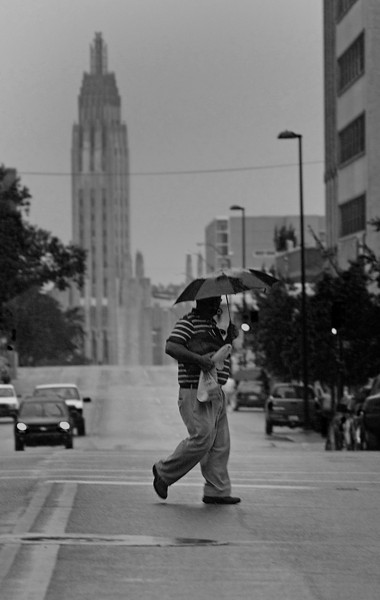 Trying to avoid getting wet during a rain shower a pedestrian uses his umbrella as he crosses Boston Avenue in downtown Tulsa.