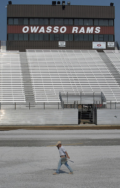 A workmen walks across a sea of gravel  used as a foundation for a turf replacement project at the Owasso High school football stadium.
