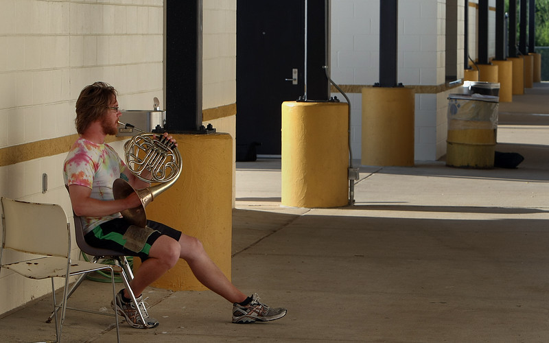 Taylor Townsen, an instructor with the national touring Cavaliers Drum and Bugle Corp, gets in a little practice on the French horn before a performance in Broken Arrow.