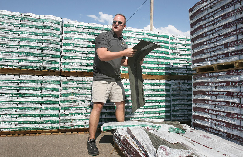 Tom Martens, sales person for Crossroads Roofing picks out shingles for a customer Thursday. PHOTO BY MAIKE SABOLICH