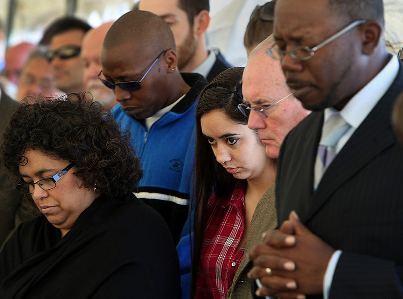 Audience members bow their heads in prayer at the Greater Cornerstone Community Development Project ground breaking on a 20,698 square-foot community center