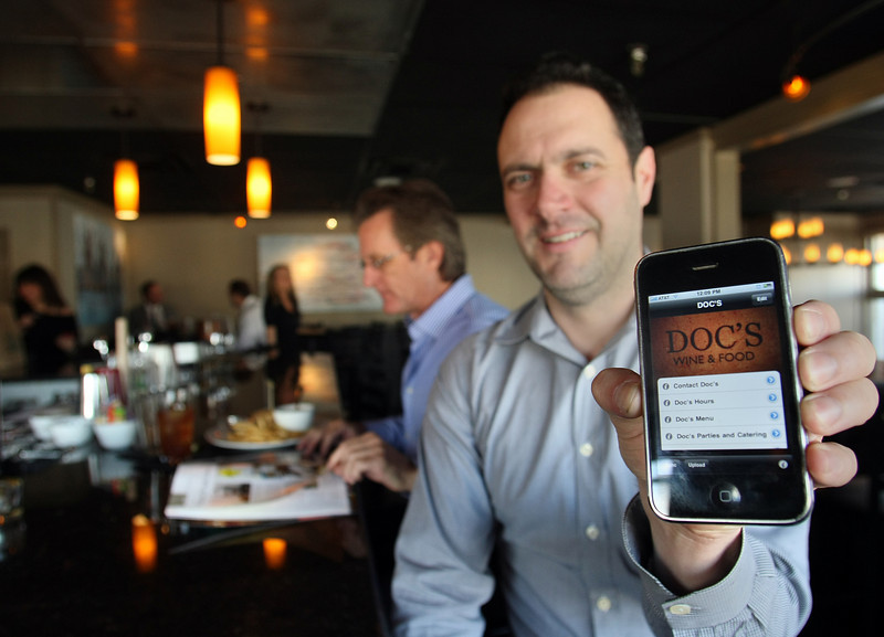 Darin Ross, Owner of Doc's Wine & Food, displays the I phone application he uses to drive business to his restaurant in Tulsa.