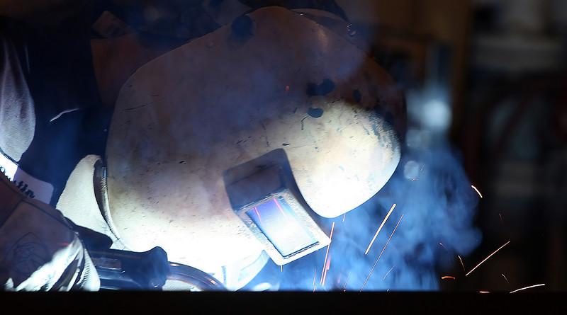 A welder at Darby Enterprises assembles a tube bending machine.