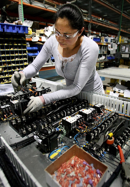 AAON employee Georgina Guzman assembles a control panel on a 240 Air Conditioning Unit.