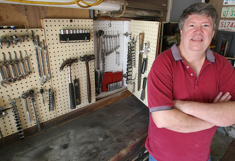 John Ellis next to his prototype of the Hid-N-Slide tool cabinet he is working to bring to market.  The cabinet uses the space between the studs in wall to store additional tools.