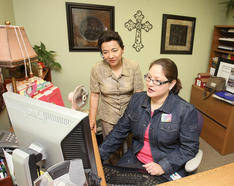 Community Health Improvement Specialists Carmen Romo and Corina Ramirez work at Integris Health Hispanic Initiative Tuesday. PHOTO BY MAIKE SABOLICH