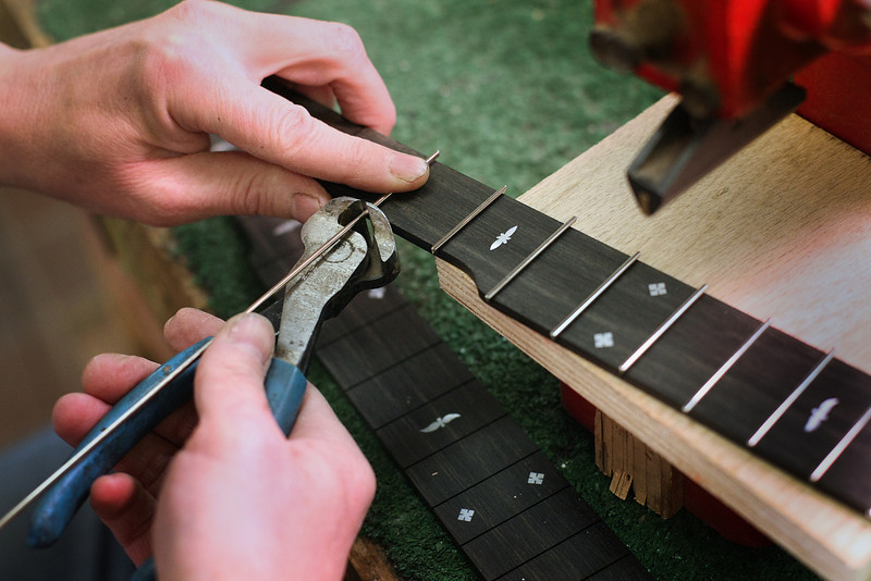 Rob Bishline, Owner of Bishline Banjos, builds a fret for one of the companies Patriot model.