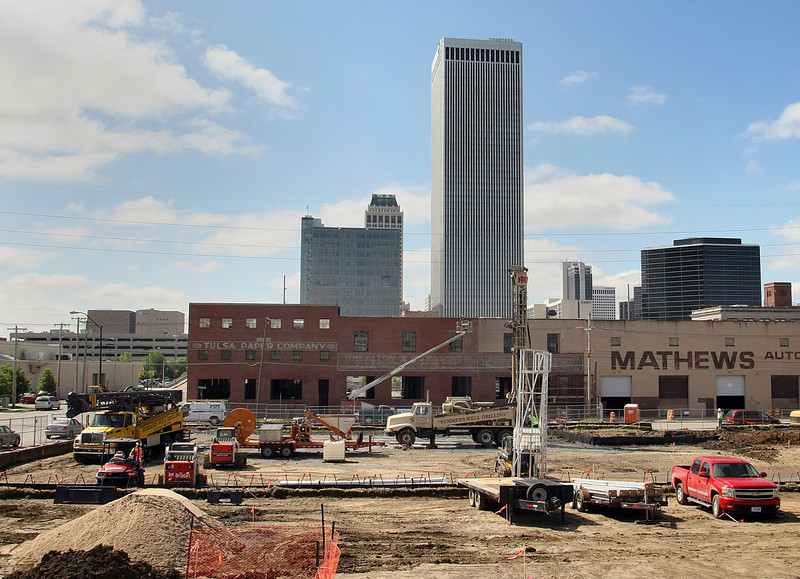 The downtown Tulsa skyline behind the drilling rigs Park on Brady construction project.