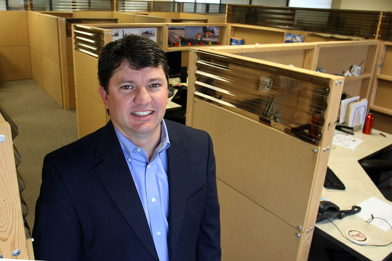 CEO of Macro Source Clint Parr stands in the many cubicles built to accommodate his growing staff.