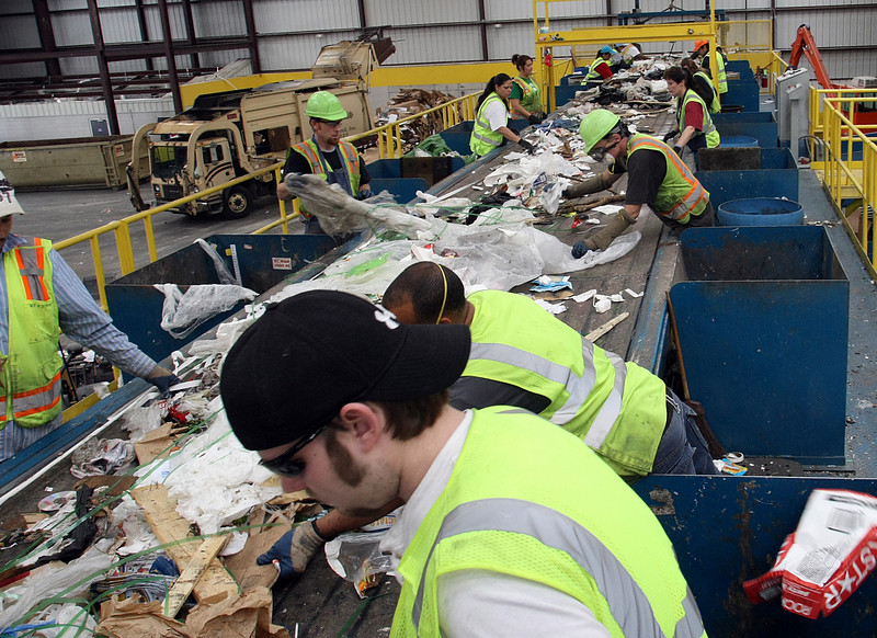 Workers at the Tulsa Recycle and Transfer facility in North Tulsa sort through trash to reclaiming recyclable materials.