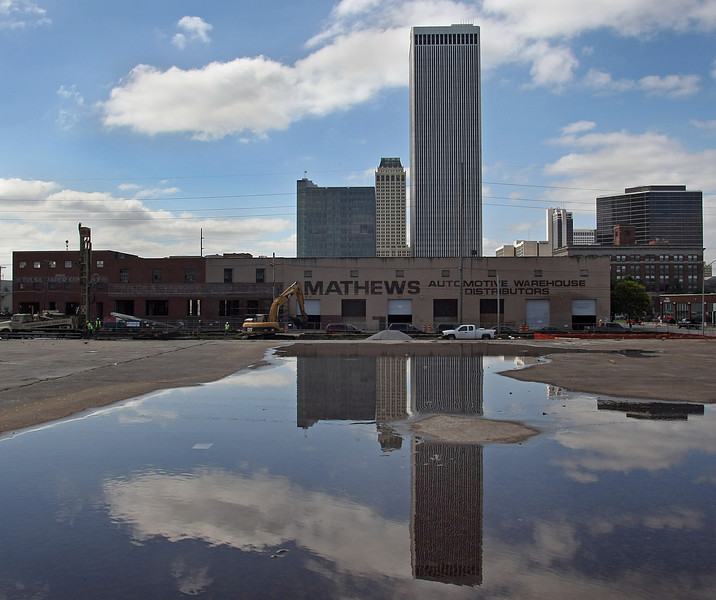 The downtown Tulsa skyline is reflected in a rain puddle at the Park on Brady construction project.