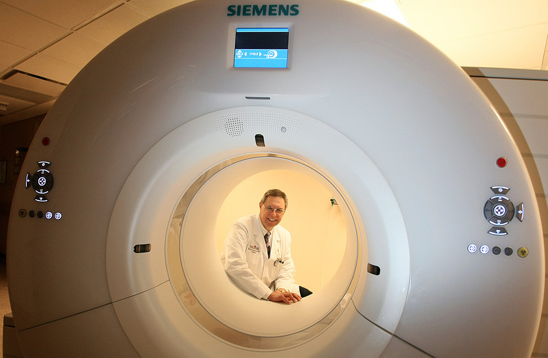 St. Anthony Hospital Radiologist Dr. Phil Stratemeier with the hospital's new CT scanner. PHOTO BY MAIKE SABOLICH