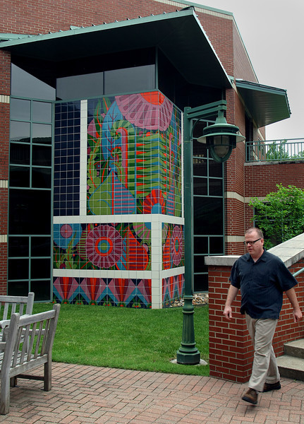 OSU Tulsa employee Ron Knight walks past some of the public artworks on display at the University.