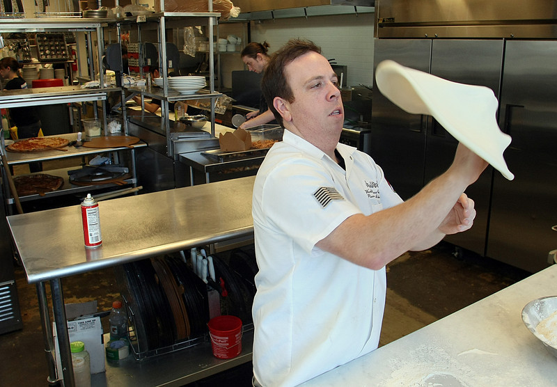 Andolini's Pizza Owner Mike Bausch throws a pizza dough as part of the preparation of the perfect pie.
