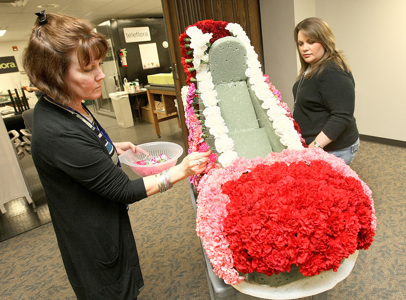 Teleflora employees Diana Bowles and Sabrina Setter work on a a shoe decorated with carnations for the weekend's marathon. PHOTO BY MAIKE SABOLICH