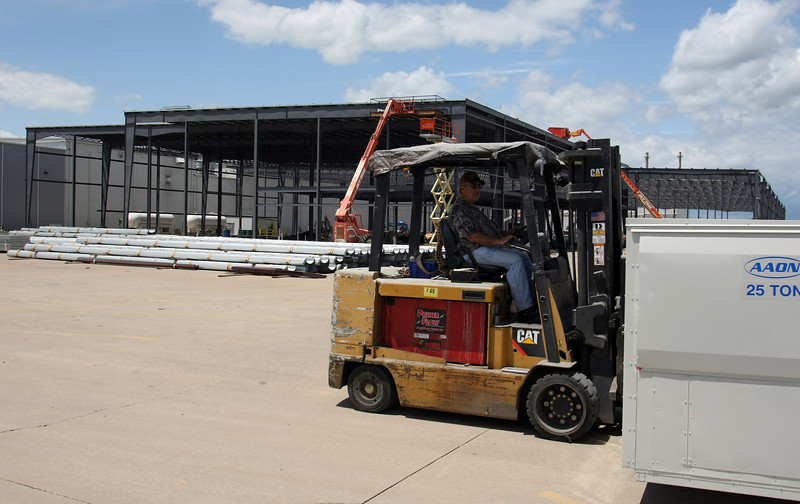 A workman moves a large air conditioning unit outside the expansion project currently underway at Tulsa based AAON.