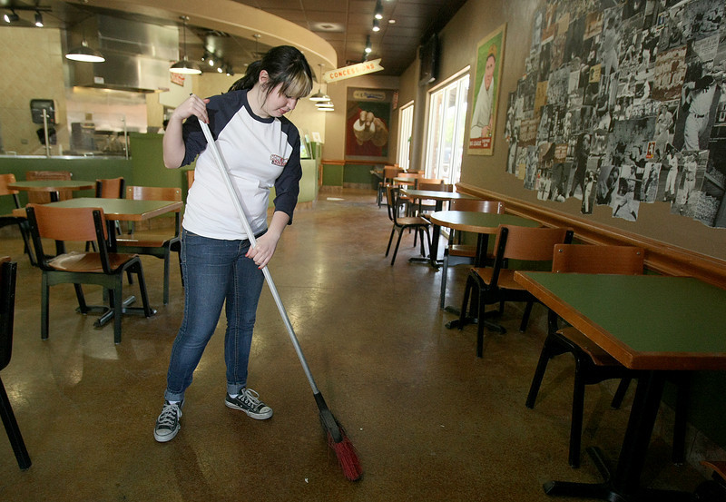 Kristen Hennessy, shift manager at Home Run Sliders in Edmond, sweeps the floors at the restaurant Friday. PHOTO BY MAIKE SABOLICH