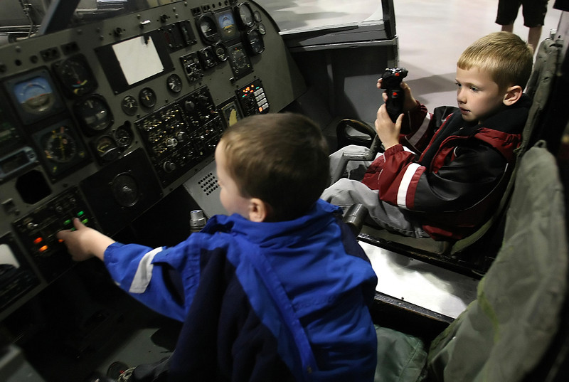 Aidan and Ethan Mapes work the switches and control joke in a T-37 simulator at the Tulsa Air and Space Museum.