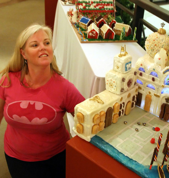 Marcy Wilson places a ginger bread house on display at the Philbrook Museum's Festival of Trees.