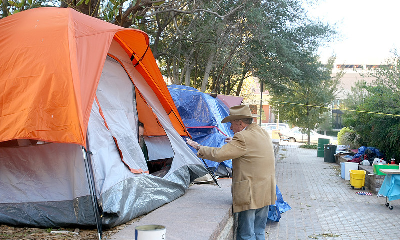 William Choate talks to someone with Occupy OKC in a tent Thursday.  PHOTO BY MAIKE SABOLICH