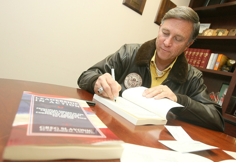 Greg Slavonic signs copies of his book Leadership in Action at the Journal Record Monday. PHOTO BY MAIKE SABOLICH