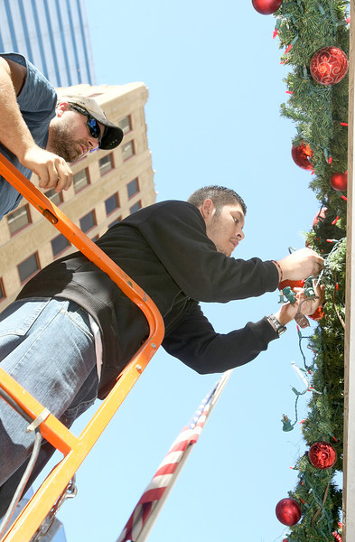 Dominic Rodriguez and Chris Obregon hang up Chrsitmas decorations at First National Building Wednesday. PHOTO BY MAIKE SABOLICH