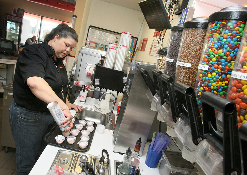Cinamon Brice, manager at Freddy's Frozen Custard in Edmond, prepares samples for the customers Tuesday. PHOTO BY MAIKE SABOLICH
