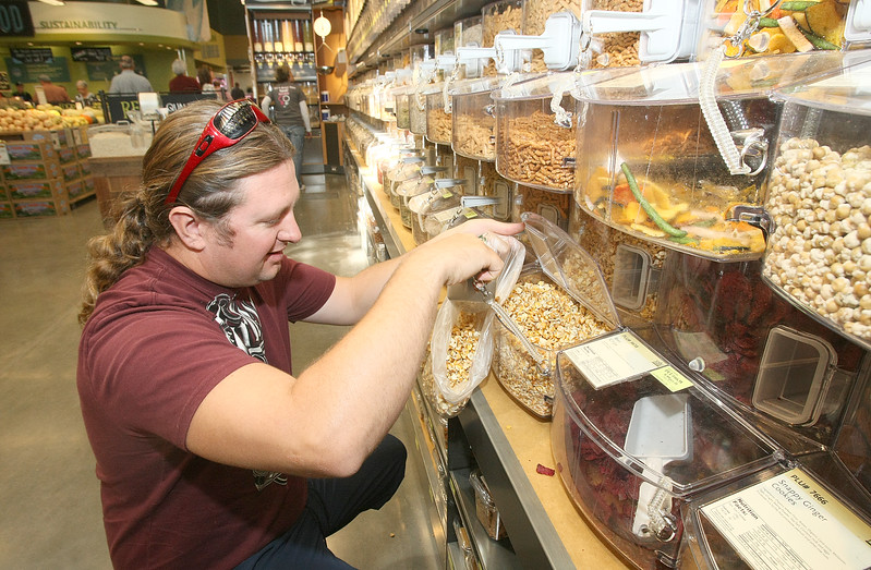 Shane Elliott fills up a bag of corn snack at Whole Foods Thursday. PHOTO BY MAIKE SABOLICH