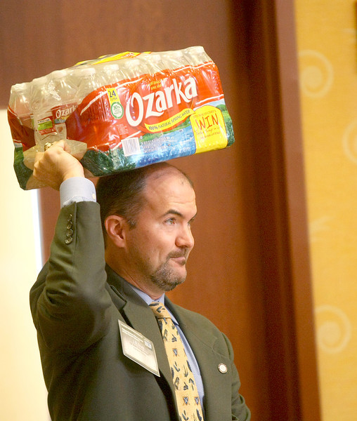 Water Board Director J. D. Strong carries a carton of bottled water at the water conference at the Embassy Suites in Norman Tuesday. PHOTO BY MAIKE SABOLICH