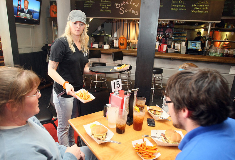 Denise McConnell, general manager at S&B Burgers, brings  food to tables Wednesday. PHOTO BY MAIKE SABOLICH