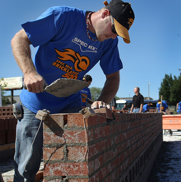 "With mortar flying from his trowel Jeff Burch of CD Commercial Masonry competes in a brick laying competition held at the TCC campus in Tulsa.  The regional competition is to determine ""who is the best bricklayer NE Oklahoma"" and to send the winners to <br /> the compete in the national competition on January 25, 2012 in Las Vegas, NV at the World of Concrete/World of Masonry Convention."