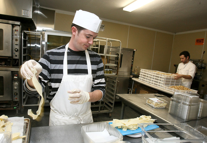 Tyler Fender with Della Terra Fine Pasta weighs pappardelle pasta for packaging Monday. PHOTO BY MAIKE SABOLICH