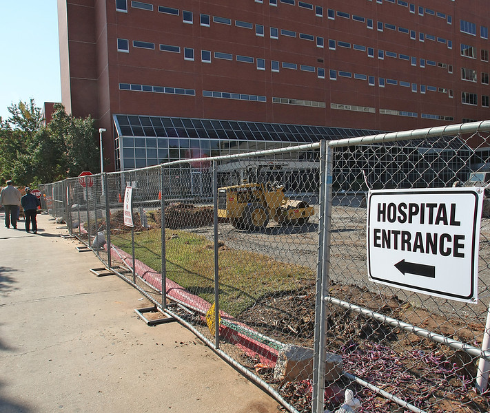 Pedestrians at the OSU Medical Center walk around construction near the main entrance of the hospital.