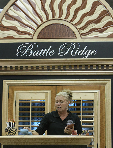 Cay Lynn Kirby works to set up the Battle Ridge Shutters booth at the Home Beautiful show at the QT Center on the Tulsa Fairgrounds.