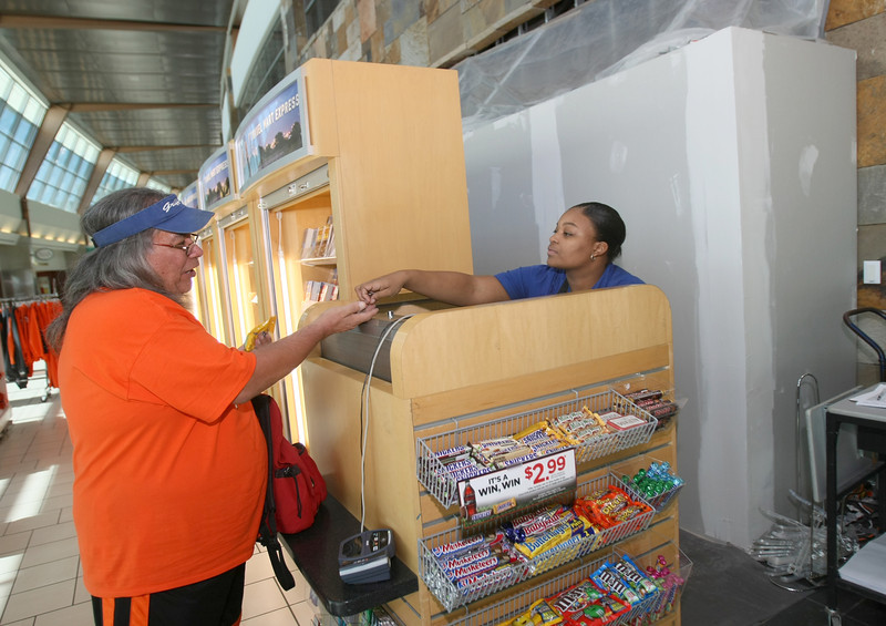 George Deer receives cash back Volley Johnson at the temporary Travel Mart Kiosk at Will Rogers International Airport Friday.  The space in the back is currently being renovated for the new Pops store.  PHOTO BY MAIKE SABOLICH